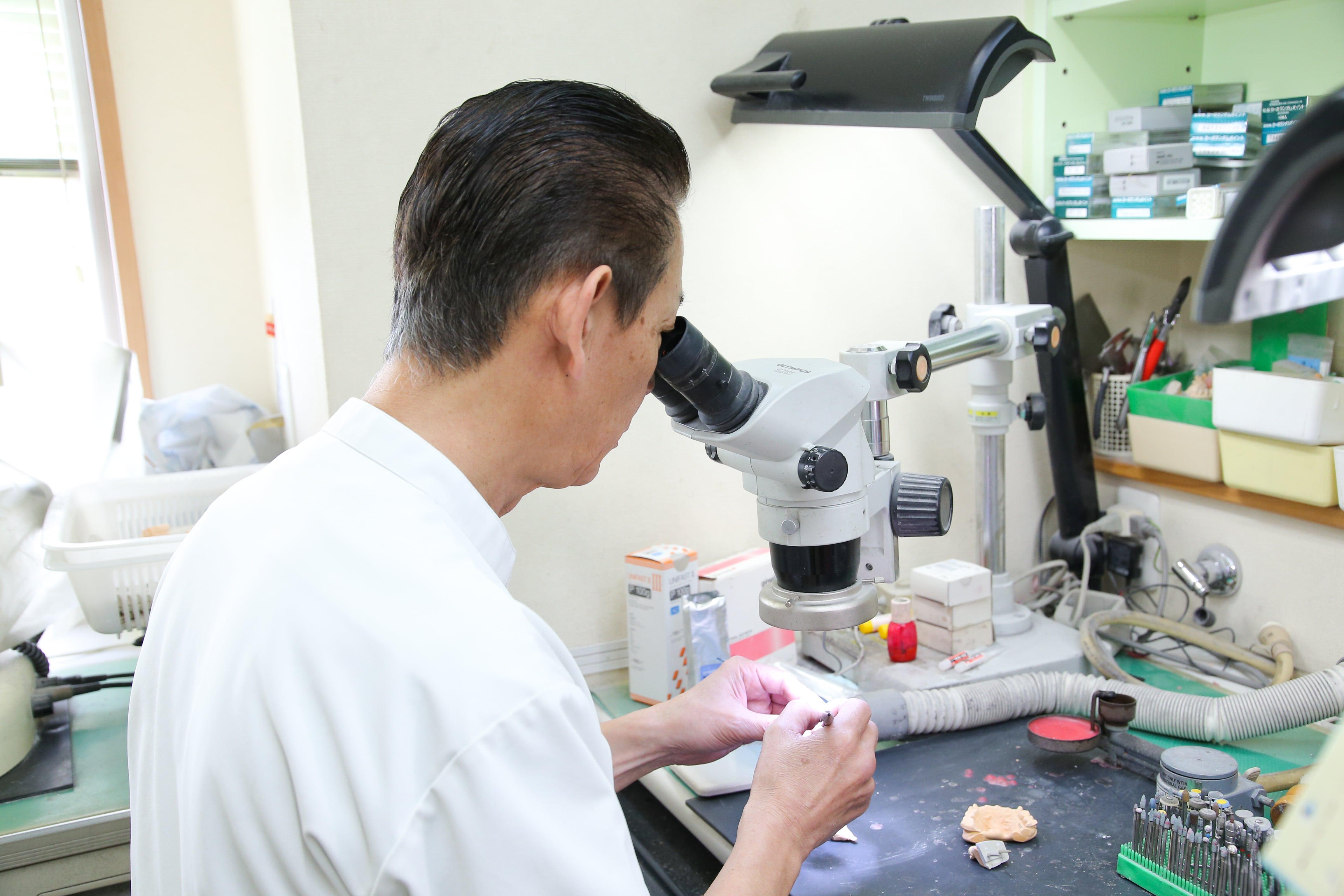 顕微鏡で観察する歯科技工士
